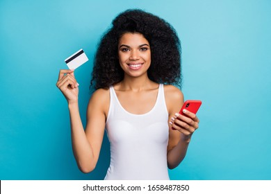Close-up portrait of her she nice cheerful cheery wavy-haired girl holding in hand card cell online internet banking service balance saving isolated on bright vivid shine vibrant blue color background
