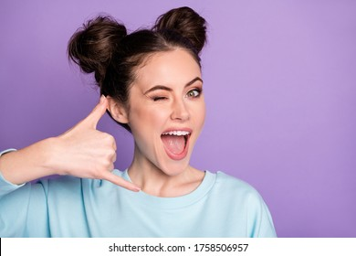 Close-up portrait of her she nice attractive cheerful girl showing gesture phone hot line center roaming operator winking isolated on violet purple lilac bright vivid shine vibrant color background