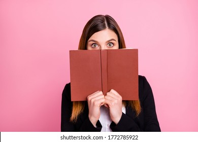Close-up portrait of her she nice attractive lovely pretty funny girlish scared red-haired schoolgirl nerd closing covering face behind book isolated on pink pastel color background