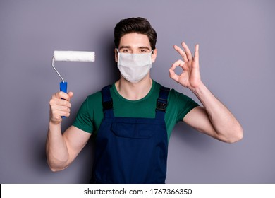 Close-up portrait of his he attractive healthy guy painter wearing safety cotton mask mers cov influenza infection prevention drawing wall building showing ok-sign isolated grey color background