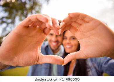 Close-up portrait of his he her she nice attractive lovely sweet cheerful cheery married spouses showing heart frame shape perfect match soulmate life partner in green wood forest