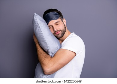Close-up portrait of his he nice attractive bearded guy holding in hands pillow drowsiness going to bed sleeping quietly calmly isolated over gray pastel violet purple background