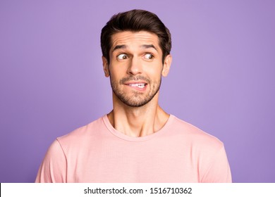 Close-up portrait of his he nice attractive funny confused brunet bearded guy wearing pink tshirt waiting news biting lip isolated over violet purple lilac pastel color background