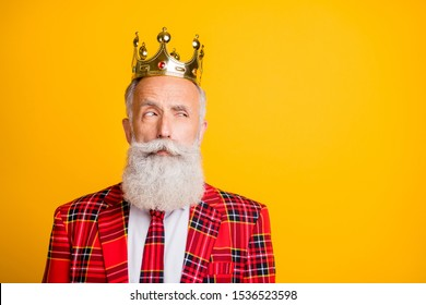 Close-up portrait of his he nice handsome attractive serious arrogant proud suspicious gray-haired man wearing crown looking aside isolated over bright vivid shine vibrant yellow color background