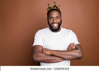 Close-up portrait of his he nice attractive cool cheerful cheery content successful bearded guy wearing white tshirt diadem folded arms isolated over dark red brown pastel color background