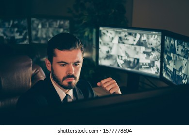 Close-up portrait of his he nice attractive qualified serious man safety expert supervising remote panel tv camera online protection management night shift late evening at work station place