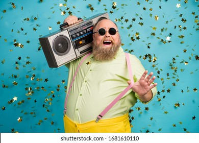 Close-up portrait of his he nice attractive cool carefree cheerful cheery funky bearded guy carrying boombox having fun confetti flying isolated over bright vivid shine vibrant blue color background