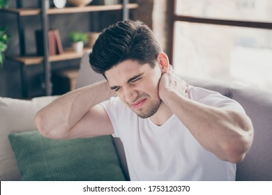 Close-up portrait of his he nice attractive miserable sick guy sitting on divan suffering touching neck pain treatment therapy massage at modern industrial loft brick interior style living-room
