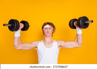 Close-up portrait of his he nice attractive sportive funky muscular nerd guy sportsman lifting heavy barbell physical intense isolated over bright vivid shine vibrant yellow color background