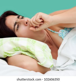 Close-up portrait of an hispanic woman coughing and resting in a bed