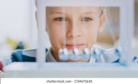 Close-up Portrait of an Inquisitive Young Boy Looking at Newton's Cradle. Child Learning about Physics