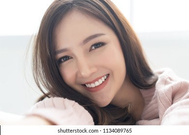 Closeup portrait of inspired caucasian Asian lady wearing knitted sweater pink cold smilling and taking selfie at her home.Concept woman lifestyle and winter. Autumn, winter season.
