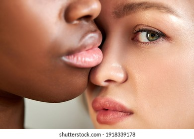 close-up portrait of interracial lgbt couple posing closely to each other, african female with big sweet lips and caucasian tender lady looking at camera