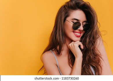 Close-up portrait of joyful brunette woman with red lips. Photo of lovable dark-haired girl in sunglasses isolated on yellow background.
