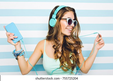 Close-up portrait of joyful girl enjoying music in big headphones, holding mobile phone in hand. Attractive young woman wearing black sunglasses and trendy accessories chilling on striped background.