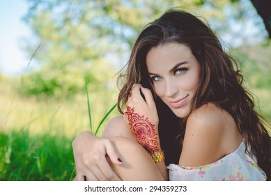 Closeup portrait of joyful glamour young pretty lady relaxing sitting on the grass and happy looking at camera