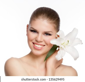Close-up portrait of joyful, smiling Caucasian girl with white flower in her hand. Beautiful and young blond woman with clean and fresh skin. Isolated on white background.