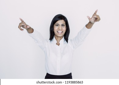 Closeup portrait of joyful young beautiful woman looking at camera, raising arms and celebrating success. Jubilation concept. Isolated front view on white background.