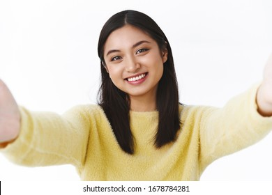 Close-up portrait of kawaii tender young asian girl taking selfie, apply photo filters, holding camera both hands sideways and smiling while video call friend with mobile phone, white background