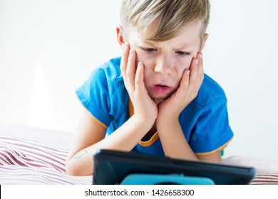 Closeup portrait of kid with fair hair in blue t-shirt watching internet TV from tablet on a bed. Theme of digital technologies