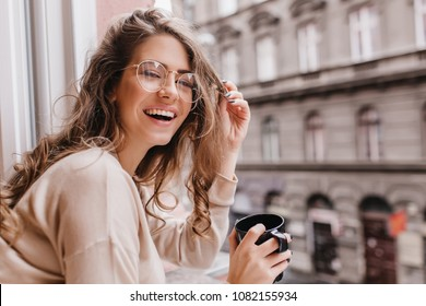 Close-up portrait of laughing brunette girl in beige sweater drinking coffee on city background. Lovable lady standing near window and looking at beautiful building with cup of tea.