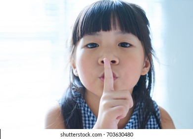 Closeup portrait of little asian chinese girl holding her finger to her lips in a gesture for silence .