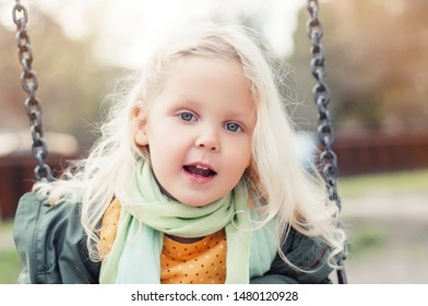 Closeup portrait of a little blonde happy girl in the outdoors. Happy childhood concept. Emotion, smile and childish mischief.