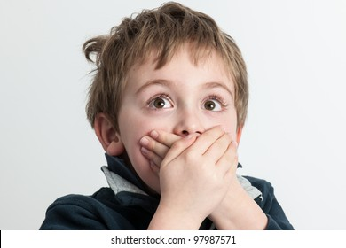 Close-up portrait of a little boy with hands on mouth - isolated on white background
