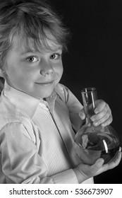 closeup portrait little boy scientist with laboratory flask on a gray background studio