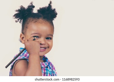 Close-up portrait of little cute baby girl learning to draw and holding brown pencil. Sweetly smiling kid posing for picture. Isolated on white background with copy space in right side