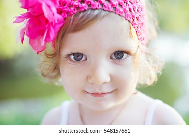 Close-up portrait of little girl with blue eyes and blond curly hair in a headband with a bright pink flower.