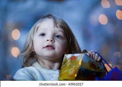 Close-up portrait of a little girl with a gift - shallow DOF, focus on eyes