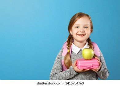 Closeup portrait of a little girl schoolgirl on a blue background. The child has a satchel behind his back and holds a lunchbox in his hands. Back to school. The concept of education.