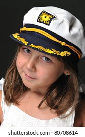 Close-up portrait of a little girl wearing a sailor's hat smiling at the camera