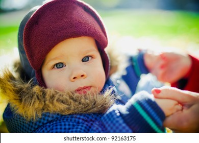 close-up portrait of a little serious boy in a cap holding his mothers arms