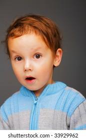 Closeup portrait of a little surprised boy in a blue sweater