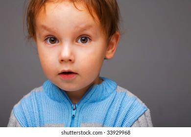Closeup portrait of a little surprised boy in a blue sweater, open attentive look