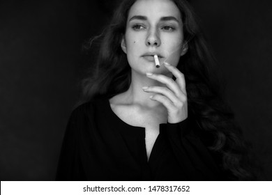 Closeup portrait of long haired curly beautiful girl. With cigarete . Black and white.
