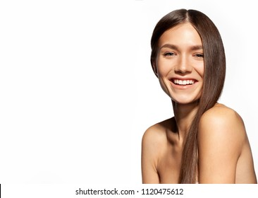 Close-up portrait of long-haired young woman with bare shoulders smiling and looking at camera with gladness. Cute beautiful girl posing at studio. Isolated on white background