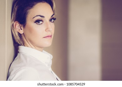 Closeup portrait of looking at camera relaxed serious middle-aged businesswoman wearing white blouse and leaning on wall. Side view.