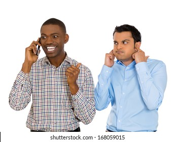 Closeup portrait of loud obnoxious rude guy talking loudly on cell phone, man next to him is pissed off and closes ears. Isolated on white background. Negative emotion facial expression feelings
