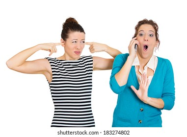 Closeup portrait loud, obnoxious rude woman, talking loudly on cell phone, girl next to her pissed off closes ears having headache Isolated white background. Negative emotion facial expression feeling