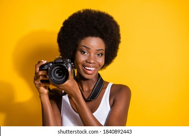 Close-up portrait of lovely cheery wavy-haired brunette girl holding in hands using digicam shooting isolated over bright yellow color background