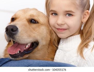 Closeup portrait of lovely little girl and golden retriever, hugging, smiling.