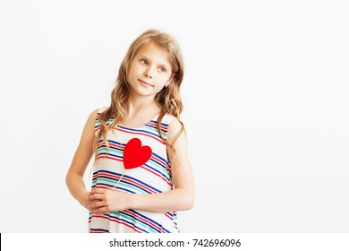 Closeup portrait of a lovely little girl against white background. Beautiful teen girl holding red paper heart. Heart ultrasound. Girls and Puberty concept. A Puberty Time line for Girls