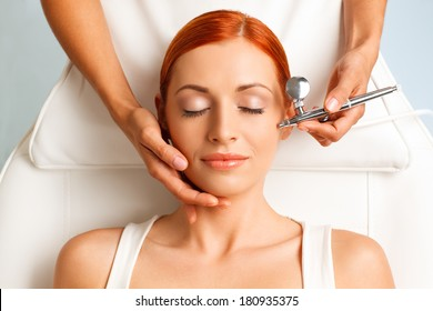 closeup portrait of lovely redheaded woman with closed eyes getting oxygen therapy in a beauty salon