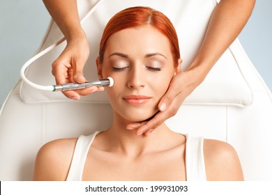 closeup portrait of lovely redheaded woman with closed eyes getting microdermabrasion procedure in a beauty salon