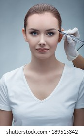 closeup portrait of lovely young woman getting permanent makeup on her eyebrows