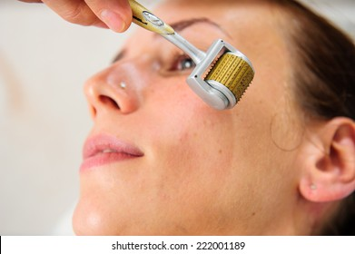 Closeup portrait of lovely young woman and hand  holding medical device touching her face .