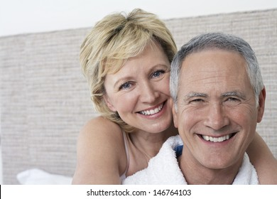Closeup portrait of loving middle aged couple smiling in bedroom